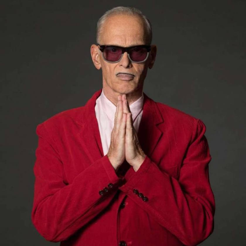 John Waters wearing sunglasses and red jacket