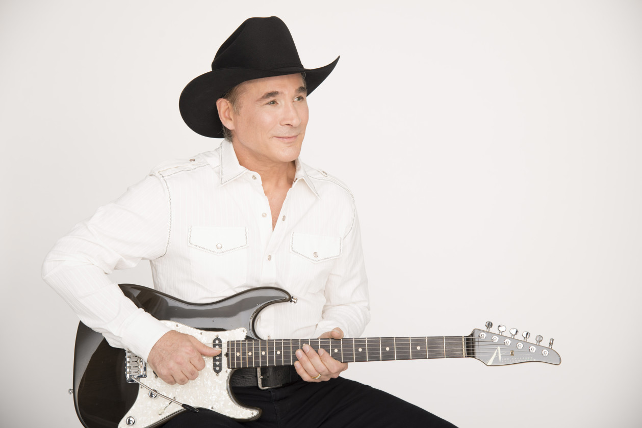 Clint Black holding guitar wearing black cowboy hat