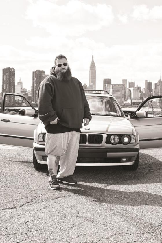 Action Bronson standing outside in front of car