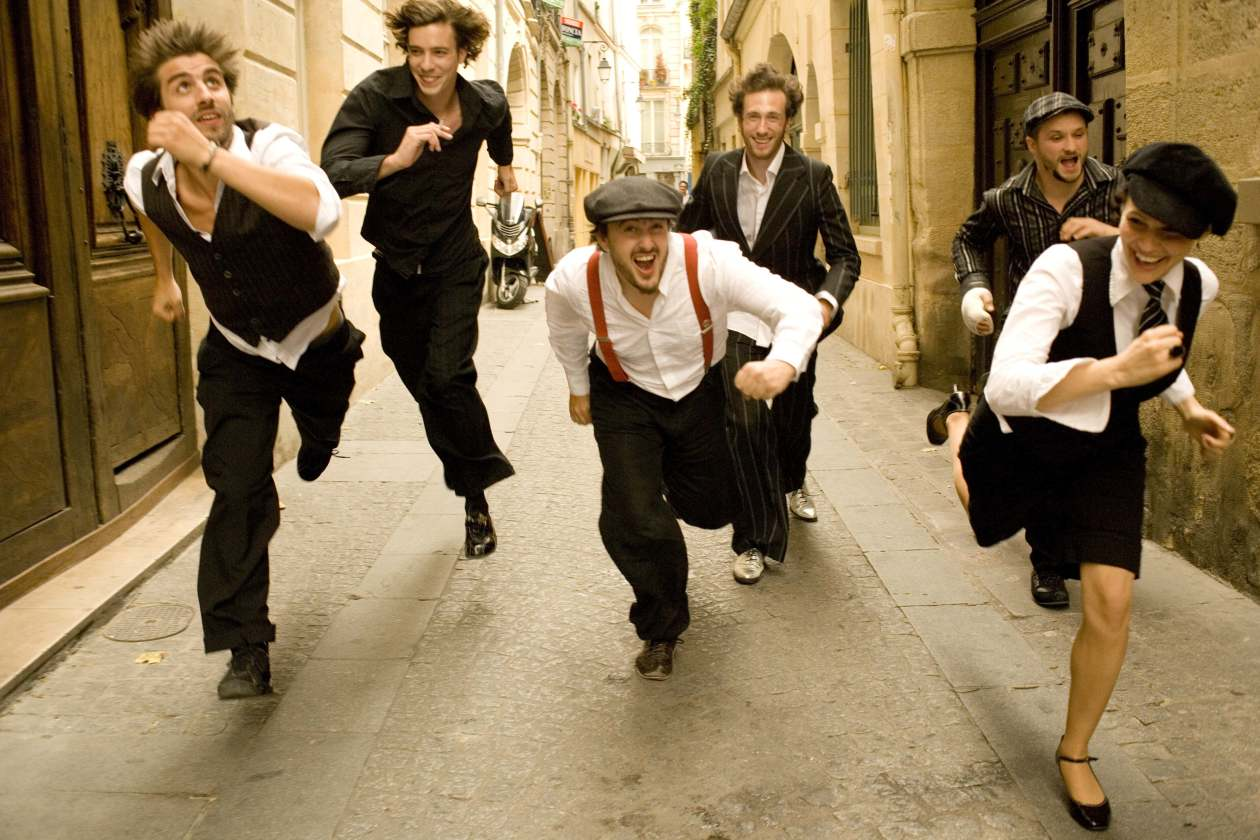 Caravan Palace group portrait running down city street