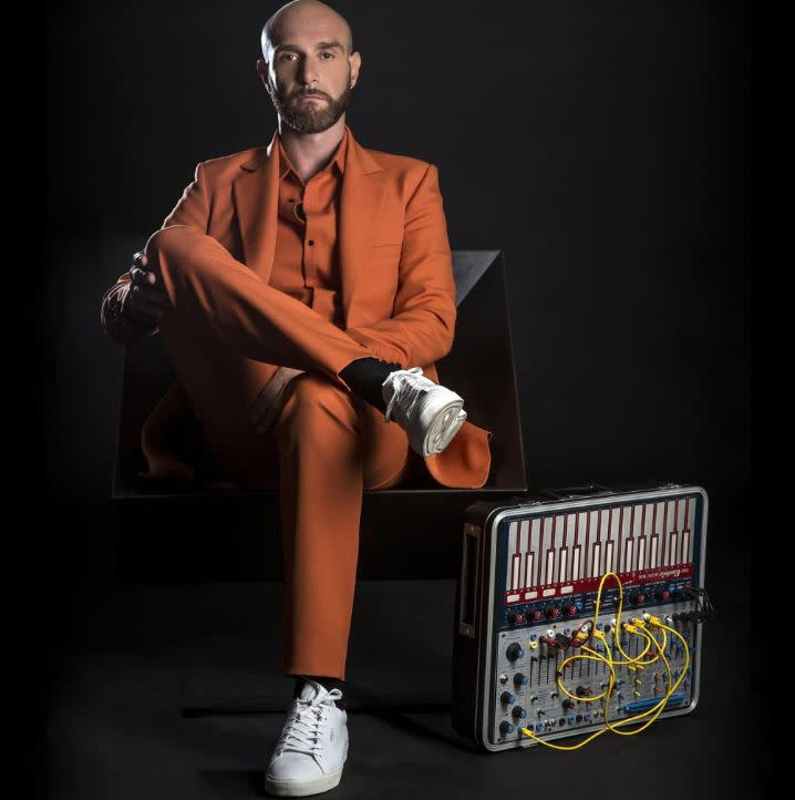 Vitalic sitting down in orange suit