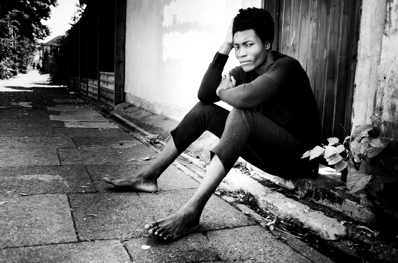 Benjamin Clementine black and white sitting outside in front of a door
