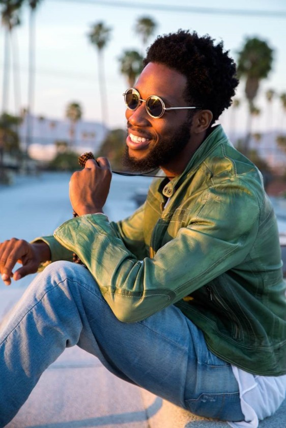 Cory Henry & The Funk Apostles sitting outside wearing green jacket