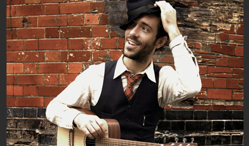 Charlie Winston with guitar in front of brick wall