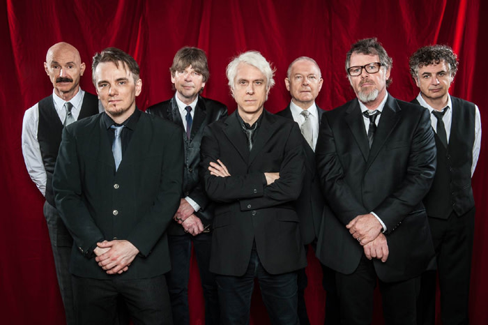 King Crimson band portrait in front of red curtain