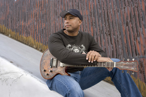 Bernie Williams sitting outside with guitar