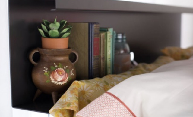 A super closeup of a decorated top bunk bookshelf on a charcoal Queen Over Queen Adult Bunk Bed.