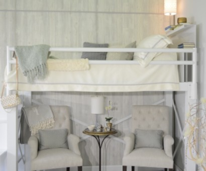 A side angle view of a full size white Adult Loft Bed focused on the bunk. Two grey chairs beneath the bed with a gold table between them.