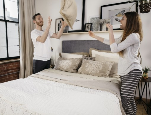 A couple is working together to dress their white Queen Standard Bed.