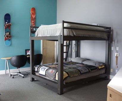 A charcoal King Over King Bunk Bed in a teenager's room.