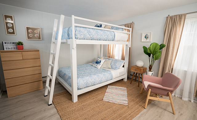 A white Queen Over Queen Adult Bunk Bed in a beach house vacation rental