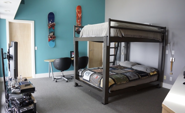 A charcoal King Over King Adult Bunk Bed in a teenager's room