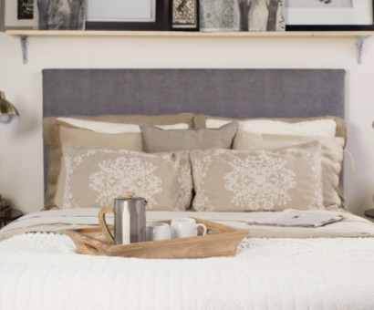 A front angle shot of a queen size Standard Bed from Francis Lofts & Bunks. There is a tray with a coffee pot and two mugs on the bed. It has a gray upholstered fabric headboard.