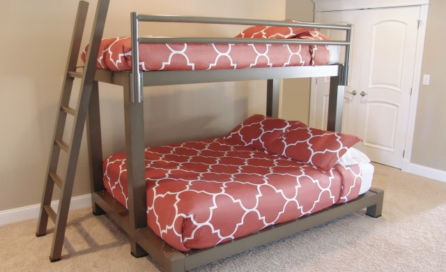 A bronze Twin Over Queen Adult Bunk Bed with red bedding.