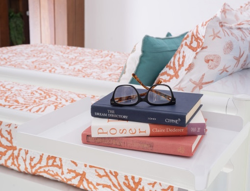 Close up of a pair of glasses resting on top of three hardcover books on a white tray accessory attached to the top bunk of a white Queen Over Queen Adult Bunk Bed.