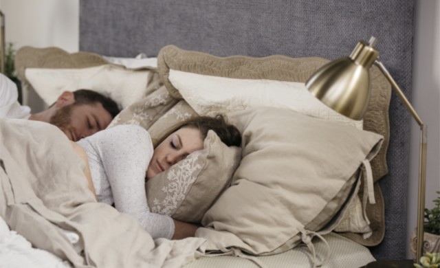 A male and female sleep together on their white Queen Standard Bed with a gray fabric headboard.