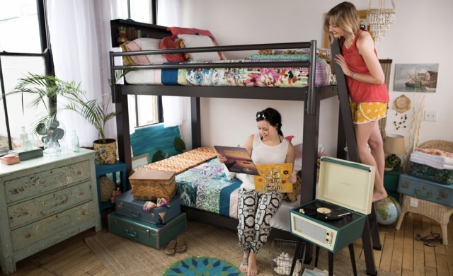 Two female roommates on a charcoal Queen Over Queen Adult Bunk Bed looking at vinyl records. One is standing on the ladder looking down at the other sitting on the bottom bunk.
