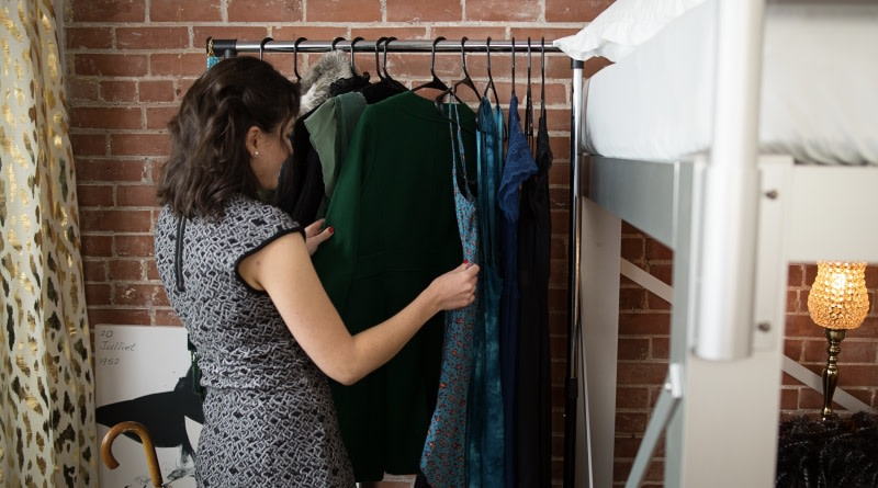 Woman Looking at Hanging Clothes - 800x445%