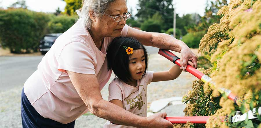 grandmother and granddaughter doing yard work together