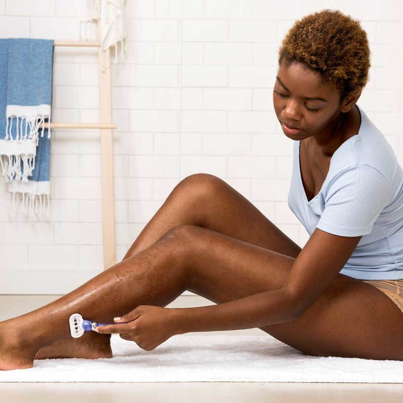 Woman Shaving Her Legs in a Bathroom with Venus Swirl Razor
