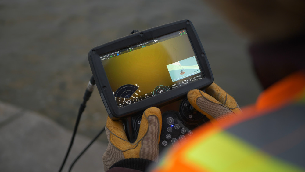 ROV pilot using controller to navigate ROV