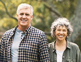 older attractive couple outside in park smiling
