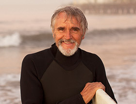 older man smiling on beach with a surf board