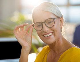 Smiling older woman adjusting glasses