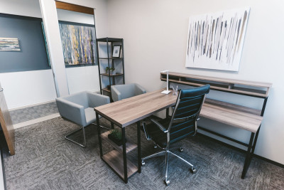 Small private office setup as an executive suite with desk and guest chairs