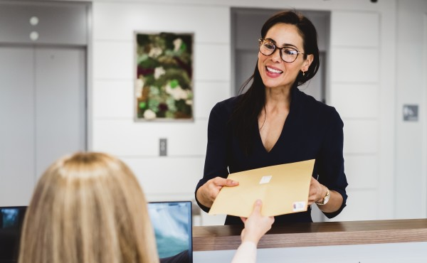 Woman receiving package from receptionist at virtual office center