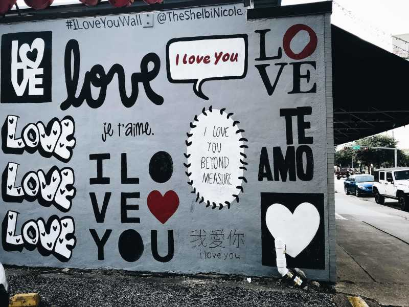 Wall with text displaying the words I love you in various ways.