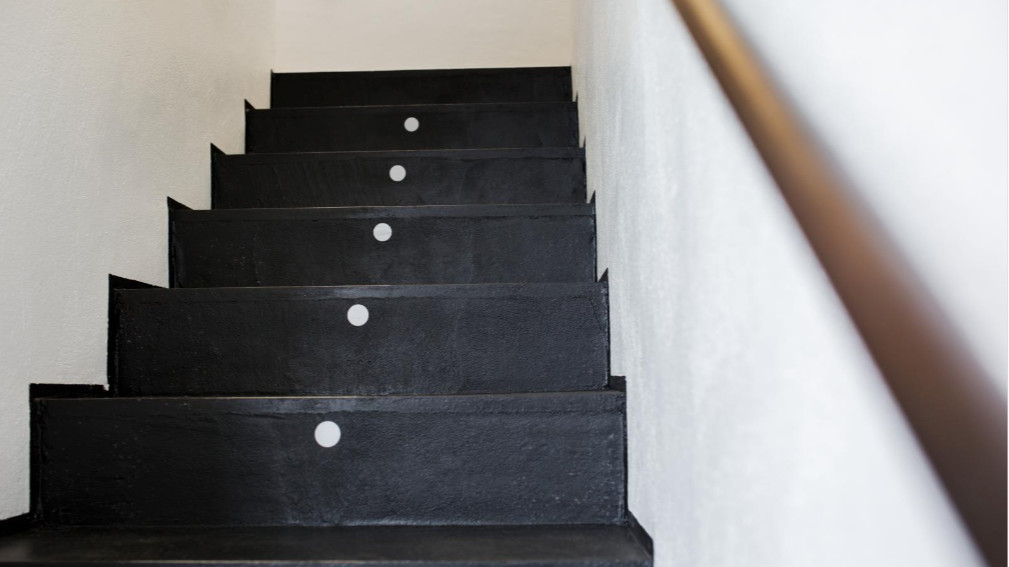 Black stairs in white stairwell and brass handrail on right.