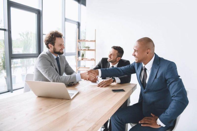 dois homens entrevistando um homen para uma vaga de emprego