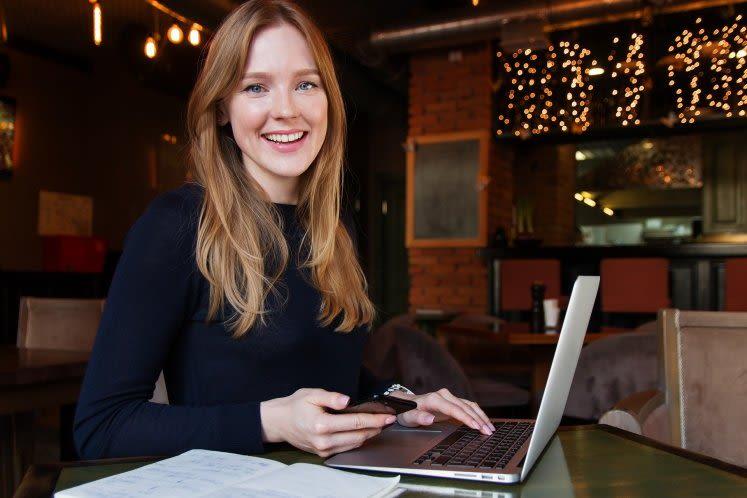 mulher branca, loira e com cabelo liso, sentada, segurando celular e sorrindo