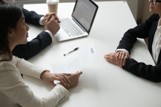 três pessoassentadas em volta da mesa, durante entrevista de emprego