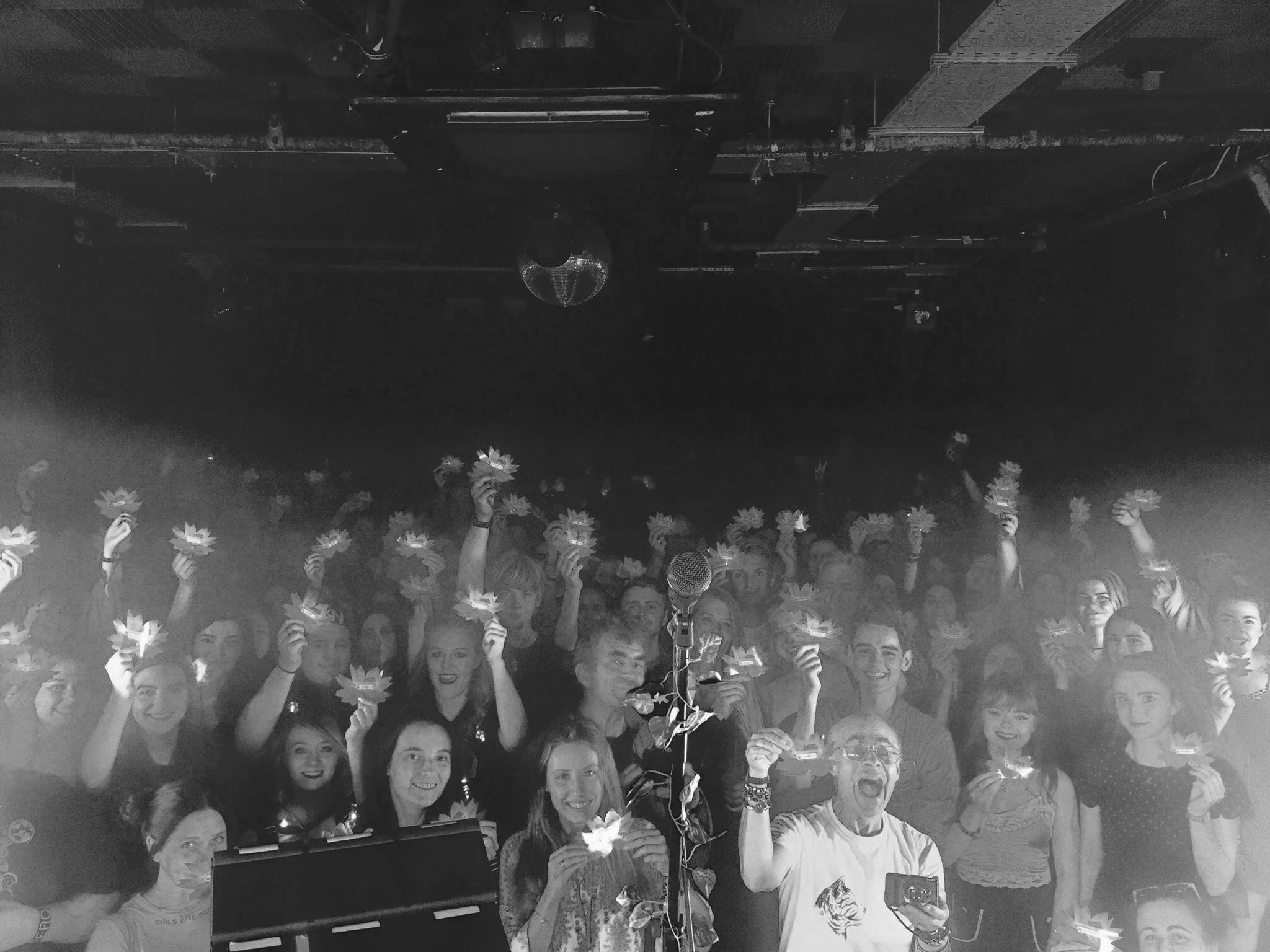 Crowd at a Nina Nesbitt show, holding up stickers featuring Spotify Codes.