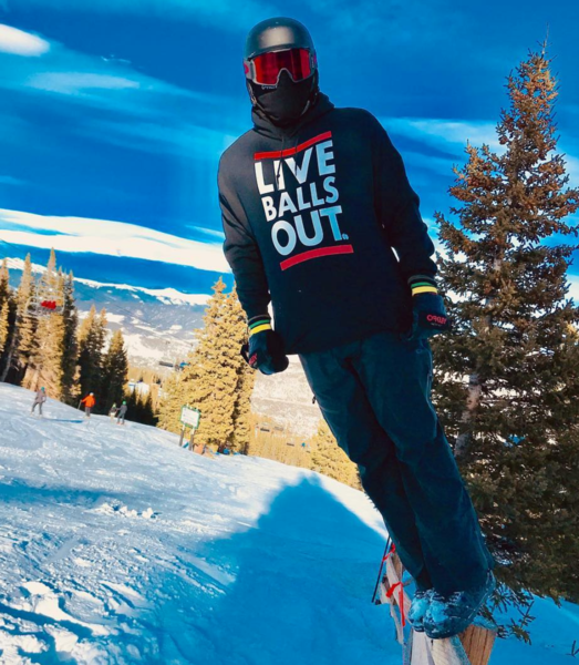 A snowboarder in a 'Live Balls Out' hoodie leans off of a wooden fence and leans as if he's about to fall towards the snow beneat