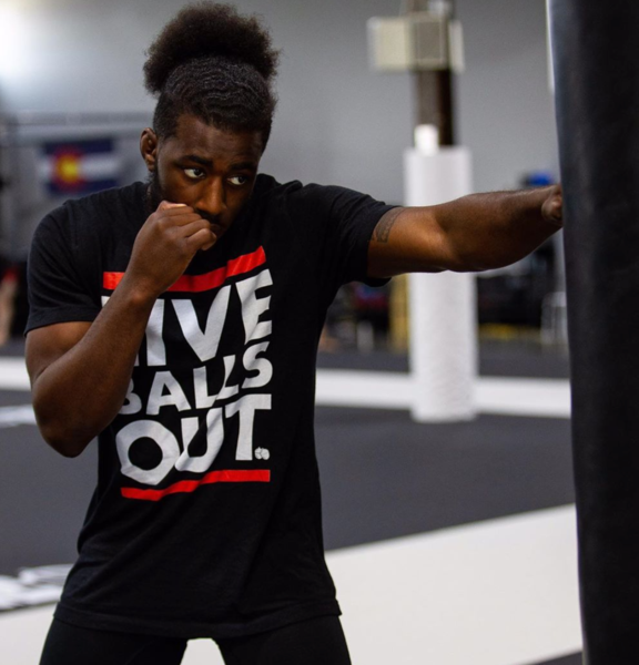 A man wearing a 'Live Balls Out' t-shirt punches a heavy bag