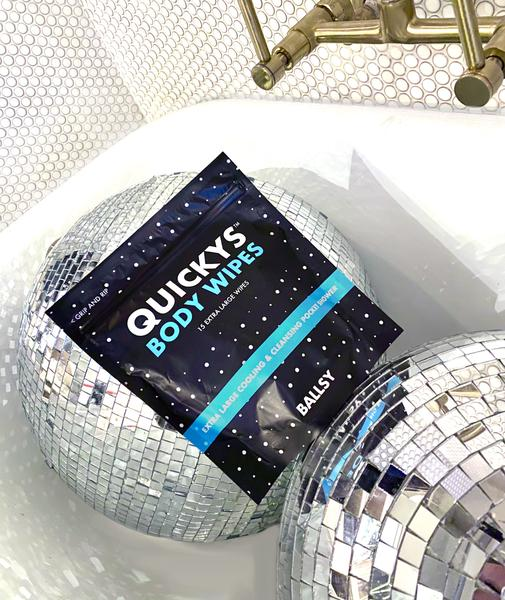 A package of Quicky's Body Wipes in a bath tub with a couple of disco balls