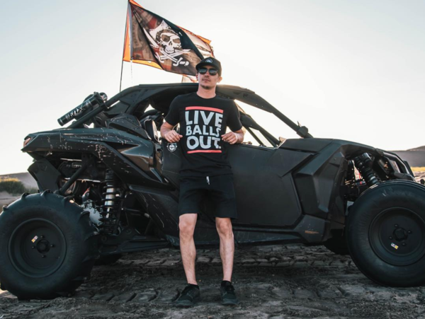 Man wearing a shirt that says 'Live Balls Out' stands in front of an off-road vehicle