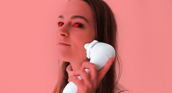 A woman with red eyes loks devilish as she uses her Clarisonic facial cleansing brush on her cheek