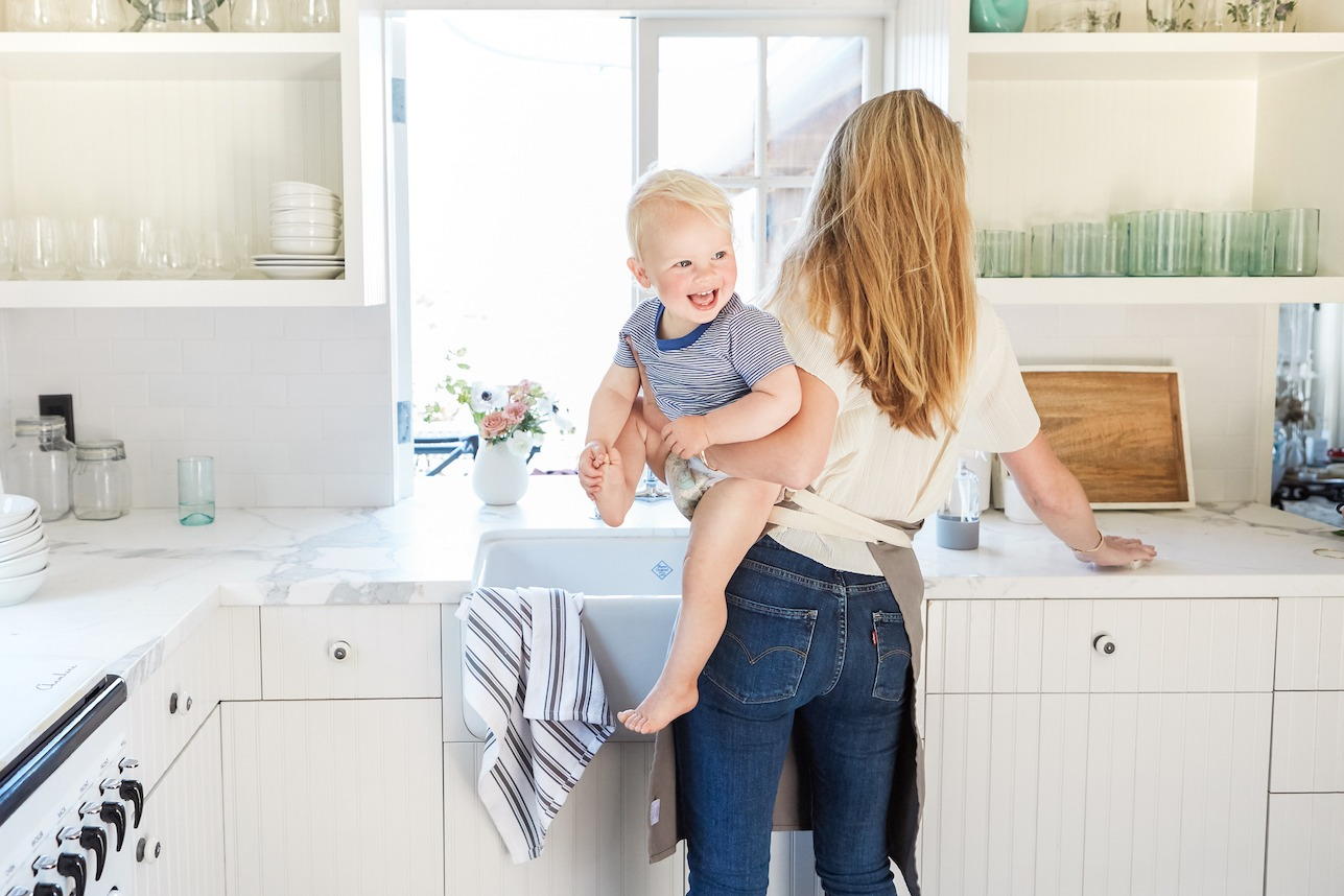 blonde mother and child wiping down counters in white kitchen