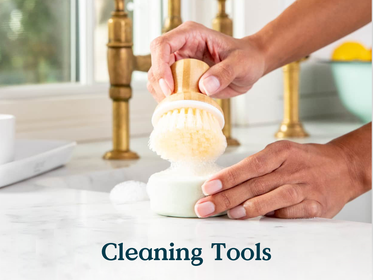 Image of kitchen sink and counter and person holding a dish brush dipped in soap