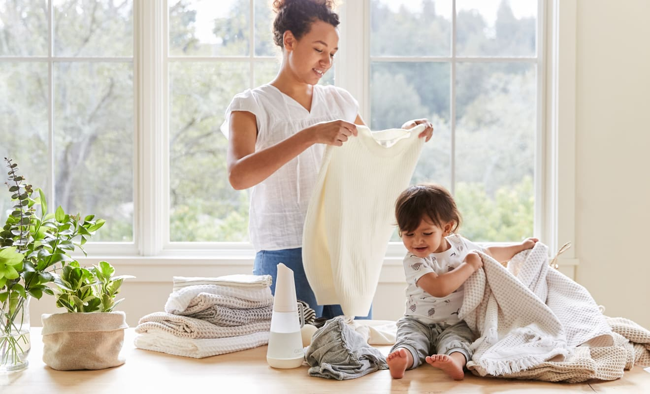 A person folds laundry with natural detergents while a young baby helps