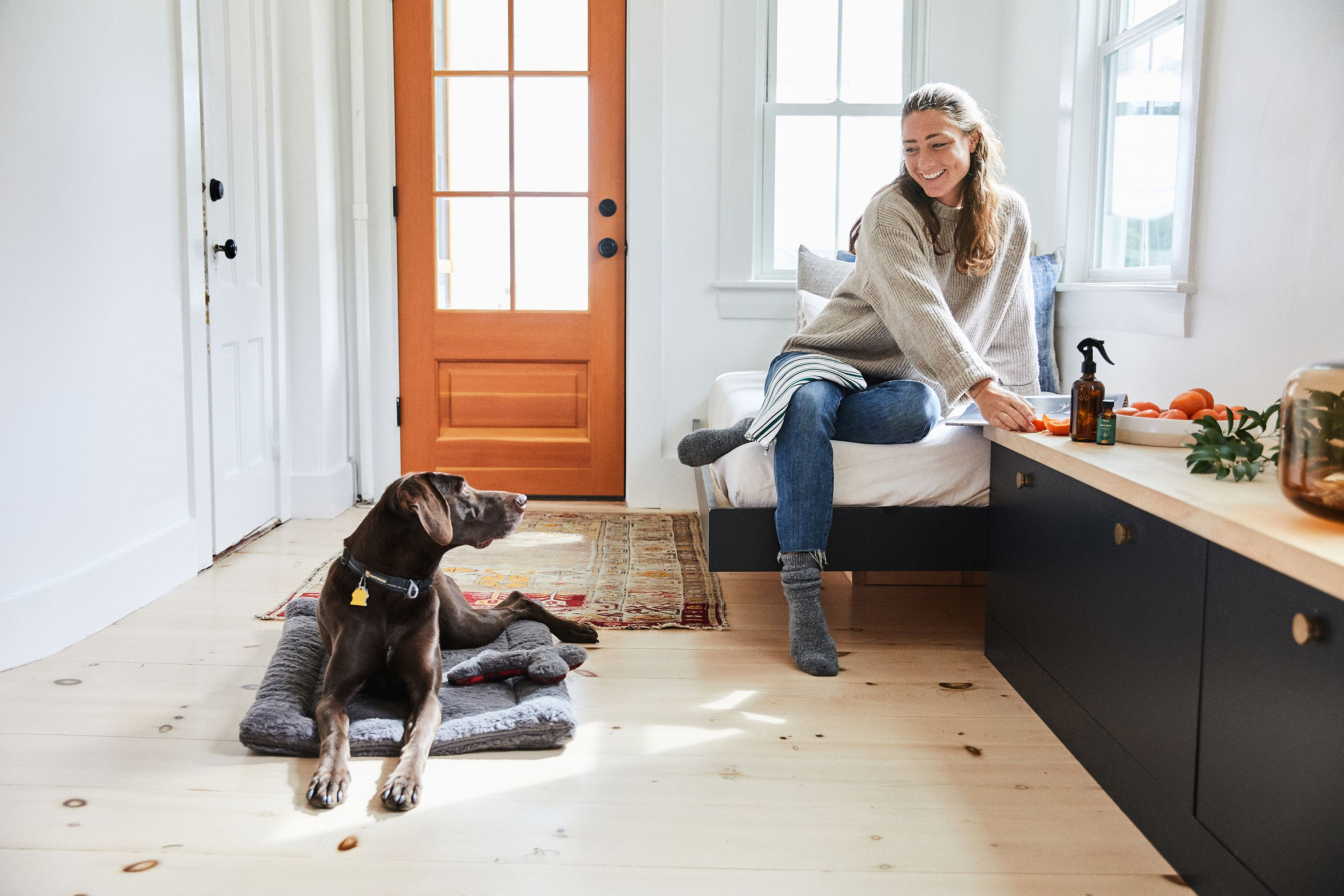 Women and dog sitting together in a home entryway