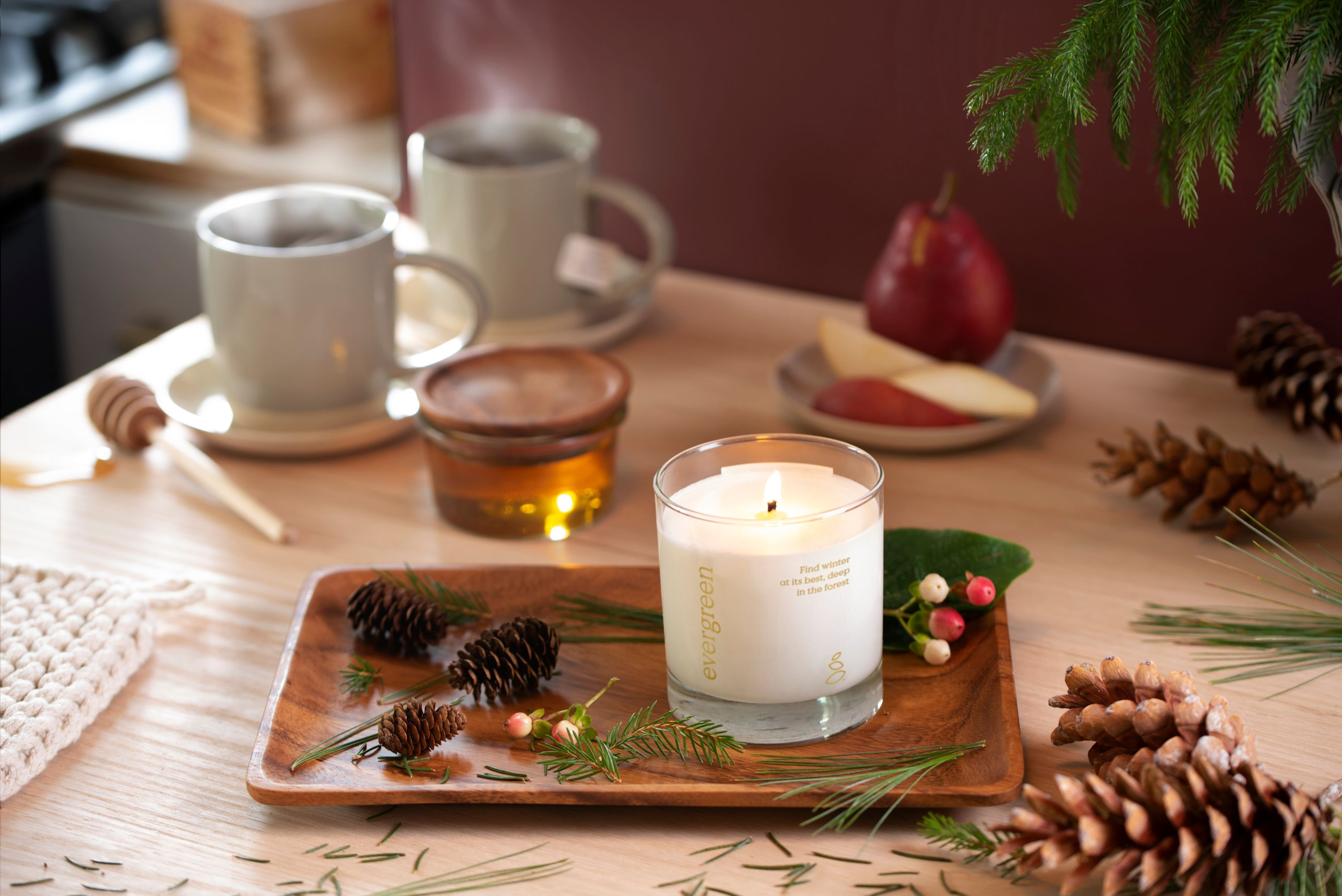 Lit candles and steaming cups of tea on a wooden table that's covered with holiday season decorations.