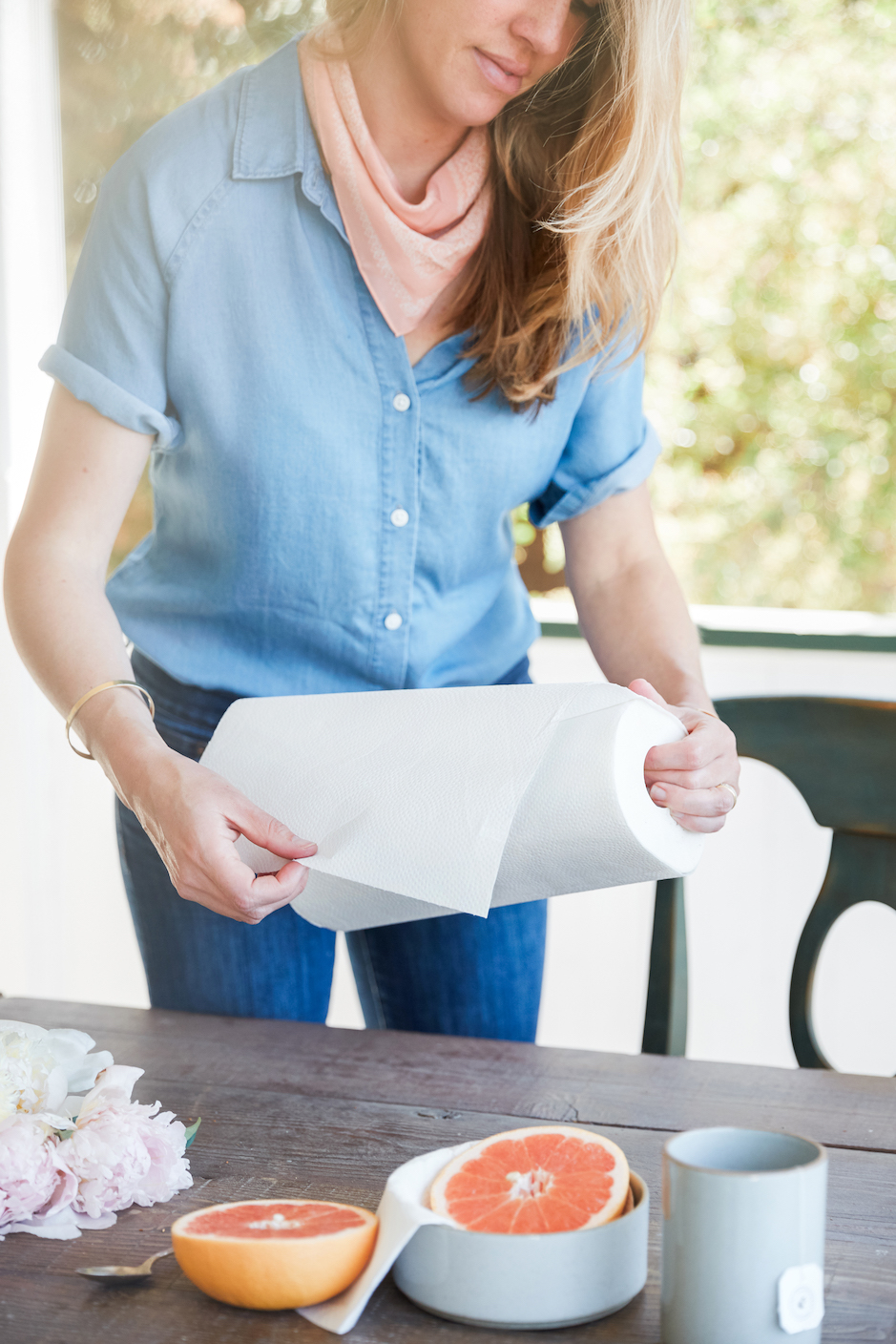woman using roll of paper towels near cut grapefruit