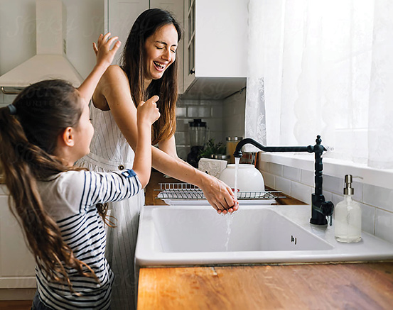 mother and daughter playing by sink in kitchen