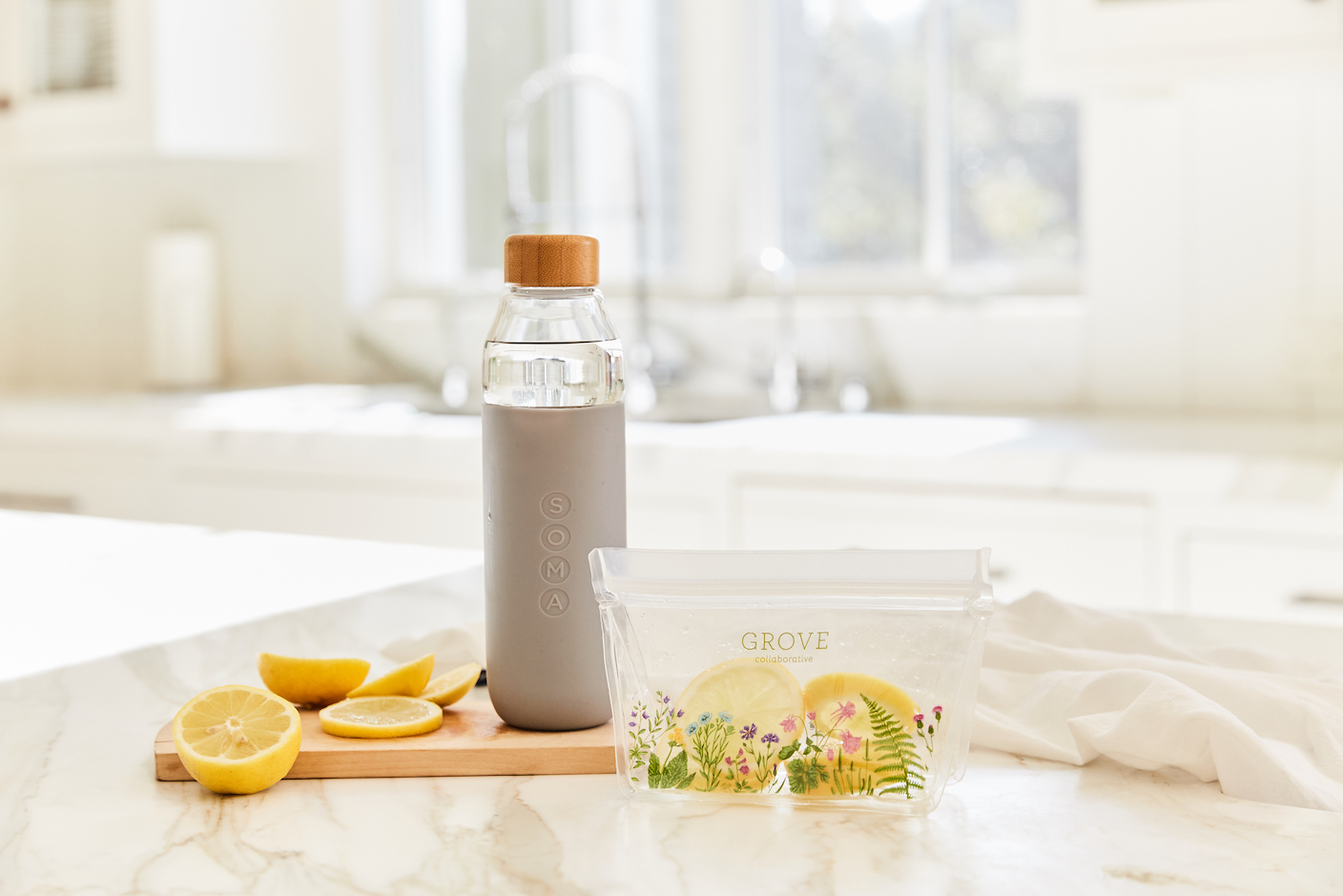 glass water bottle with silicone sleeve and reusable food bag and lemons