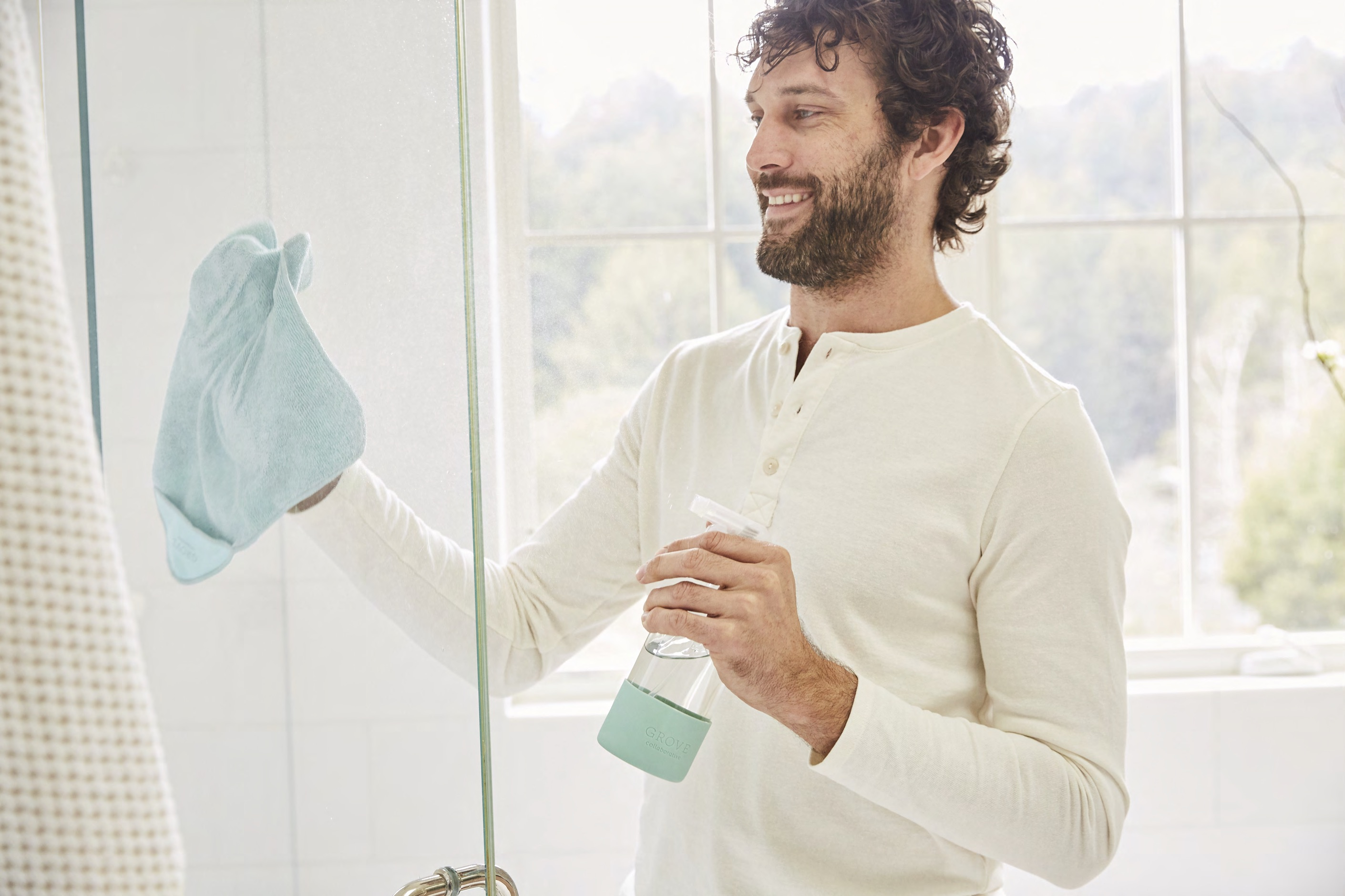 man cleaning shower with spray bottle and microfiber cloth
